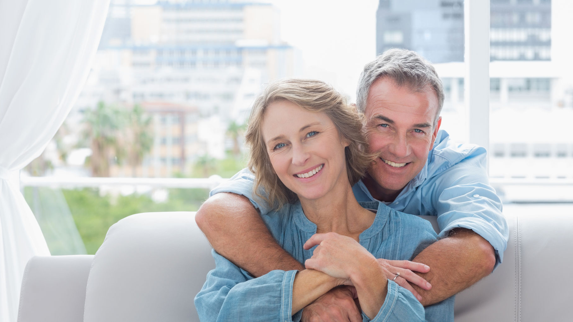 Smiling older man and woman on couch.