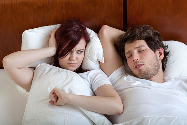 woman kept awake by man snoring from sleep apnea